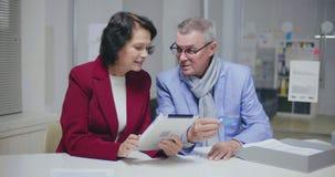 Un uomo anziano che detta il suo numero di carta di credito della moglie video d archivio