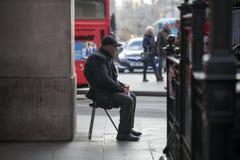Un uomo anziano che si siede all'aperto su una sedia, guardante la folla Fotografia Stock