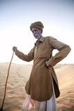 Un uomo anziano che sta su una duna, vivente nel deserto, un driver del cammello fotografia stock