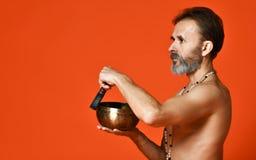 Un uomo anziano con gli Yogi grigi di una barba nella buona forma fisica tiene una ciotola di canto per yoga immagine stock