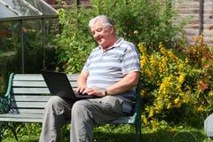 Un uomo anziano con il computer portatile all'esterno. Immagini Stock Libere da Diritti