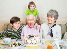 Un uomo anziano con la famiglia sta soffiando le candele sul dolce Fotografie Stock Libere da Diritti