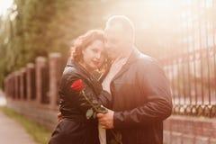 Un uomo anziano d? una rosa rossa ad una donna Una donna con le labbra rosse abbraccia un uomo Coppia sposata felice La gente in  immagini stock libere da diritti
