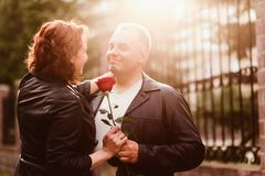 Un uomo anziano d? una rosa rossa ad una donna Coppia sposata felice La gente in lampadina immagine stock
