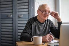 Un uomo anziano esamina lo schermo del computer portatile, fa le note in un taccuino, scrive le tasse immagini stock