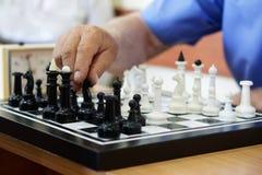 Un uomo anziano gioca gli scacchi I pezzi bianchi vincono immagini stock libere da diritti