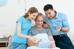 Un uomo anziano si trova in una stanza di ospedale su un letto È visto dall'uomo con una donna Fotografia Stock Libera da Diritti