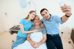 Un uomo anziano si trova in una stanza di ospedale su un letto È visto dall'uomo con una donna Fanno il selfie su uno smartphone Fotografia Stock