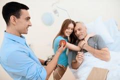 Un uomo anziano si trova in una stanza di ospedale su un letto È visto dall'uomo con una donna La donna sta abbracciando l'uomo a Immagine Stock