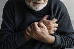Un uomo anziano sta avendo un attacco di cuore con dolore toracico immagini stock