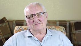 Un uomo anziano sta sedendosi in una sedia e sta mettendo sui vetri stock footage