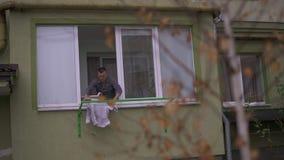 Un uomo appende per asciugare i vestiti sulla via Sera piovosa bagnata Prepara per l'arrivo della sua moglie Aiuta la sua moglie  stock footage