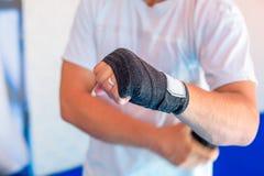 Un uomo avvolge le fasciature di sport sulle sue mani fotografia stock