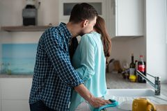 Un uomo bacia una donna nel collo nell'interno della cucina piatti del Co-lavaggio, persone appena sposate in una nuova casa immagini stock libere da diritti
