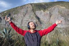 Un uomo barbuto ascolta musica sulle cuffie, in natura Dietro lui sono le montagne L'uomo ha sparso le sue armi È felice immagini stock libere da diritti