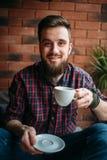Un uomo barbuto beve il caffè in caffè immagini stock libere da diritti