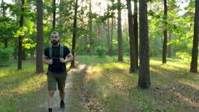 Un uomo barbuto con uno zaino cammina lungo un sentiero nel bosco Dietro lui, il tramonto viaggio nave Movimento lento video d archivio