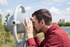 Un uomo barbuto guarda tramite il binocolo pubblico fotografia stock