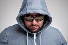 Un uomo barbuto misterioso in occhiali da sole si è nascosto sotto un cappuccio Immagini Stock