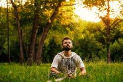 Un uomo barbuto sta meditando su erba verde nel parco Immagine Stock Libera da Diritti