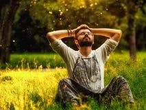 Un uomo barbuto sta rilassandosi su erba verde nel parco Fotografie Stock