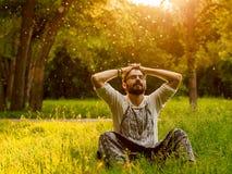 Un uomo barbuto sta rilassandosi su erba verde nel parco Immagini Stock Libere da Diritti