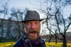 Un uomo barbuto in un cappello grida nella sorpresa fotografie stock