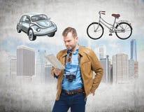 Un uomo bello in abbigliamento casual tiene una mappa e pensa al modo più adatto per il viaggio o la permuta nella città Sketc Fotografie Stock