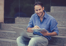 Un uomo bello che si siede sui punti con il computer portatile e un blocco note Fotografia Stock Libera da Diritti