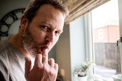 Un uomo bello che tira un fronte sciocco con il suo dito nel suo mout fotografia stock