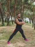 Un uomo bello con stoppia che fa l'allungamento si esercita in una foresta sexy, uomo muscolare caldo di sport che cammina nel pa Immagini Stock Libere da Diritti