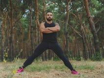 Un uomo bello con stoppia che fa l'allungamento si esercita in una foresta sexy, uomo muscolare caldo di sport che cammina nel pa Immagini Stock