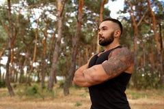 Un uomo bello con stoppia che fa l'allungamento si esercita in una foresta su uno sfondo naturale vago Fotografia Stock