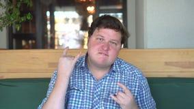 Un uomo bello e grasso con il grande ente mostra il segno dei corni nel caffè o nel ristorante archivi video