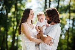 Un uomo bello e la sua giovane bella moglie tenere la loro piccola figlia nelle armi sull'aria fresca nella foresta immagini stock