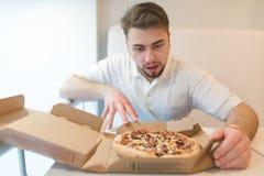 Un uomo bello fissa alla pizza con uno sguardo affamato L'uomo sta andando prendere un pezzo di pizza Fotografia Stock Libera da Diritti