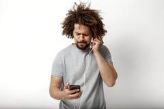 Un uomo bello riccio che porta una maglietta grigia sta esaminando il telefono e sta ascoltando le cuffie sopra il bianco immagine stock