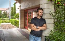 Un uomo bello si appoggia fuori della sua costruzione che gode della vista fotografia stock
