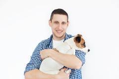 Un uomo bello sorridente che tiene un cane di razza su un fondo bianco Il concetto della gente e degli animali giovane che tiene  immagine stock