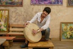 Un uomo bello sta giocando un tamburino Immagini Stock