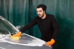 Un uomo bello sta lavando un'automobile fotografia stock libera da diritti