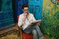 Un uomo bello sta leggendo un giornale Fotografia Stock