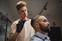 Un uomo bello sta ottenendo un taglio di capelli dal parrucchiere su un fondo del parrucchiere Un tipo attraente nel salone di be fotografia stock