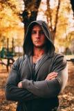 Un uomo bello sta in un parco di autunno in abiti sportivi fotografia stock