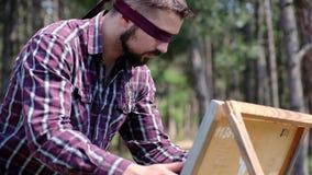 Un uomo bendato sta lavorando appassionato alla sua immagine, essendo nel legno archivi video