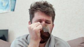 Un uomo beve il tè con il limone e le tosse Ha il raffreddore, emicrania, febbre, brividi stock footage