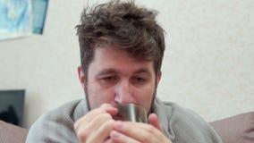 Un uomo beve il tè con il limone Ha il raffreddore, emicrania, febbre, brividi video d archivio