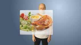 Un uomo bianco sceglie i piatti per lanciare tramite uno schermo virtuale Fragrante delizioso fritto pollo del pesce della pasta  stock footage