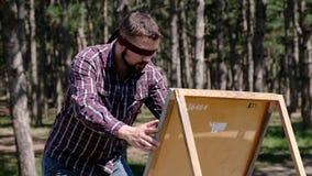 Un uomo blondfolded fa entusiasta gli schizzi su una tela mentre è nel legno video d archivio