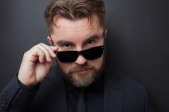 Un uomo brutale con una barba e un'acconciatura alla moda in un vestito nero esamina terribile la macchina fotografica, cadente i fotografia stock